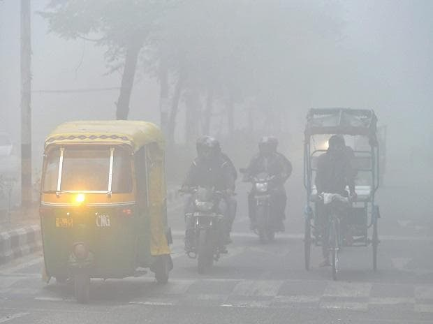 People commute in thick fog in New Delhi on Sunday morning