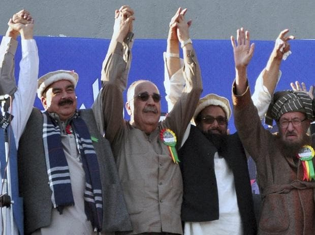 In this Dec. 29, 2017 photo, Palestinian Ambassador to Pakistan Walid Abu Ali, second left, raises jointly hands with Hafiz Saeed, second right, the head of the hard-line Jamaat-ud-Dawa, and others during an anti-US rally in Rawalpindi, Pakistan. Pho