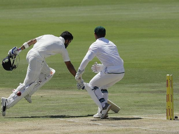 India's captain Virat Kohli, left, runs home safely to avoid a run out. Photo: AP/PTI