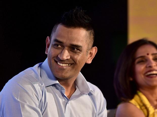 Chennai Super Kings (CSK) skipper MS Dhoni flanked by India Cements Director Rupa Gurunath reacts during an event
