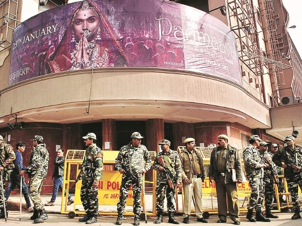 Security personnel stand guard outside a cinema house after the release of the film