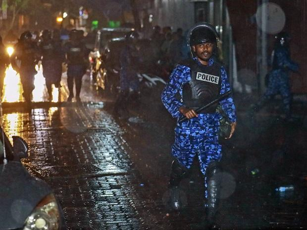 A Maldives policeman charges with baton towards protesters after the government declared a 15-day state of emergency in Male, Maldives