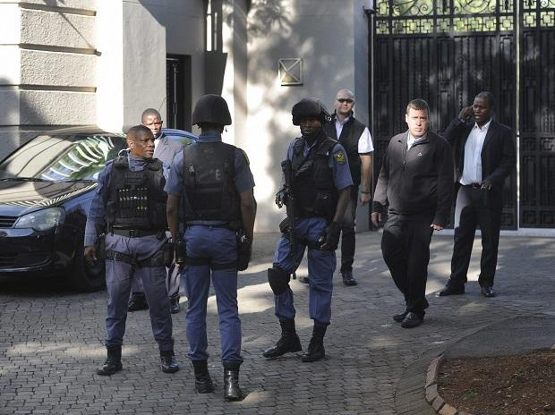 South African police exit after a raid on a home in Johannesburg. (Photo: AP/PTI)