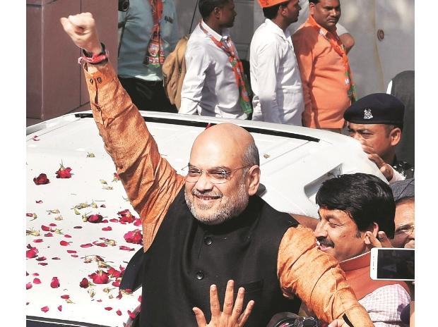 BJP President Amit Shah greets party workers as they celebrate outside the party headquarters in New Delhi. (Photo: PTI)