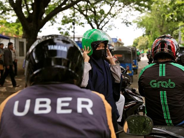 A passenger of Grab bike fixes her helmet next to Uber driver at Manggarai train station in Jakarta, Indonesia. (Photo: Reuters)