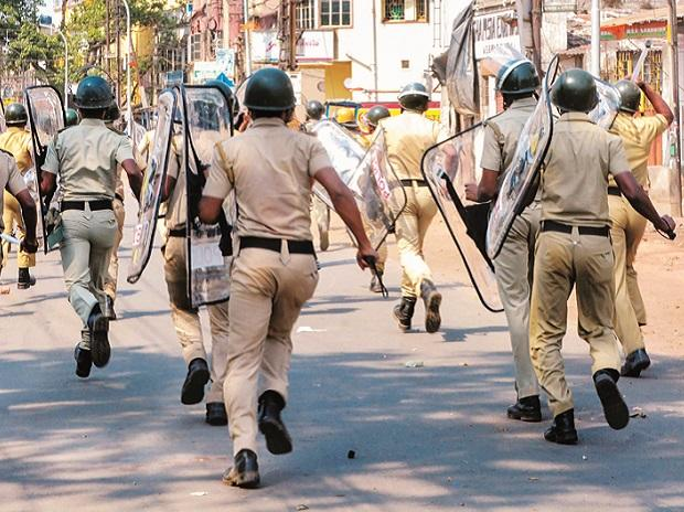 Police personnel chase away miscreants after clashes and incidents of arson over a Ram Navami procession at Raniganj in Burdwan district on Monday. Photo: PTI