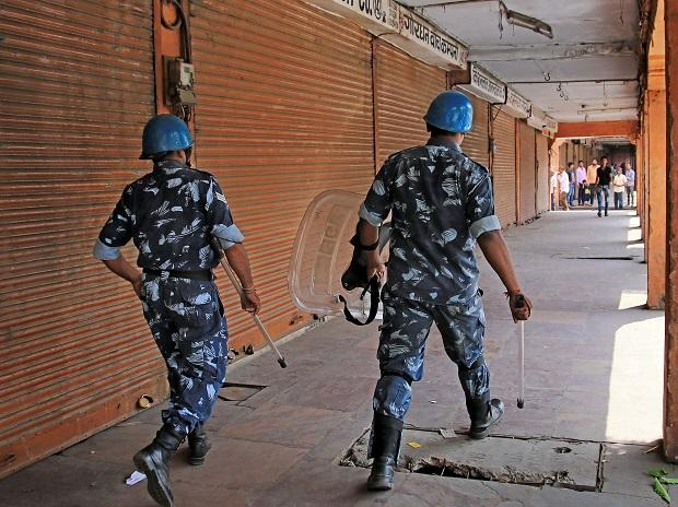 Rapid Action Force personnel walk past closed shops at wall city during 'Bharat bandh' over Scheduled Castes/Scheduled Tribes reservation issue, in Jaipur. Photo: PTI