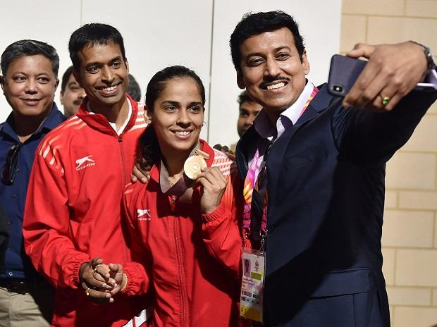 Sports Minister Rajyavardhan Singh Rathore takes selfie with the women's singles badminton gold medalist Saina Nehwal during the Commonwealth Games 2018, in Gold Coast, Australia on Sunday