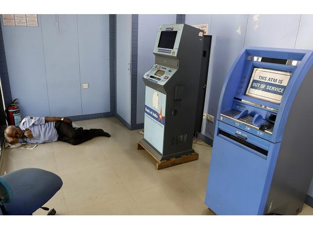 A security guard sleeps near an 'out of service' ATM machine in Ahmedabad. Photo: PTI