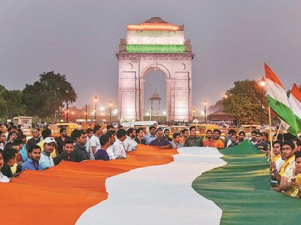 People hold a 200-ft-long Tricolour while taking part in a 'Tiranga March' to protest alleged communalisation of Kathua rape case, at India Gate in New Delhi on Saturday. Photo: PTI