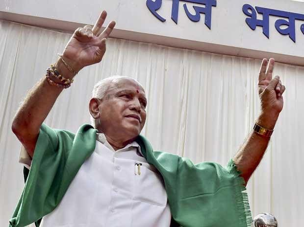 Karnataka Chief Minister B S Yeddyurappa flashes the victory sign after his swearing-in ceremony, at Raj Bhavan in Bengaluru