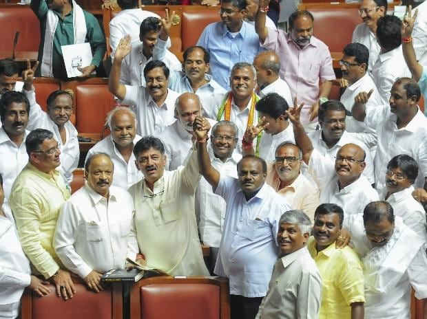 JD(S) leader HD Kumaraswamy and party MLAs show victory sign to celebrate after chief minister BS Yediyurappa announced his resignation before the floor test, at Vidhana Soudha, in Bengaluru, on Saturday