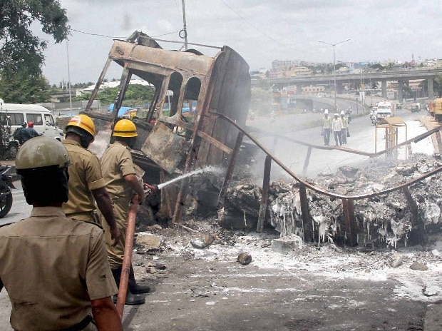 Fire men dousing a torched truck in Bengaluru on Tuesday, a day after violent protests by pro-Kannada activists over Cauvery water row