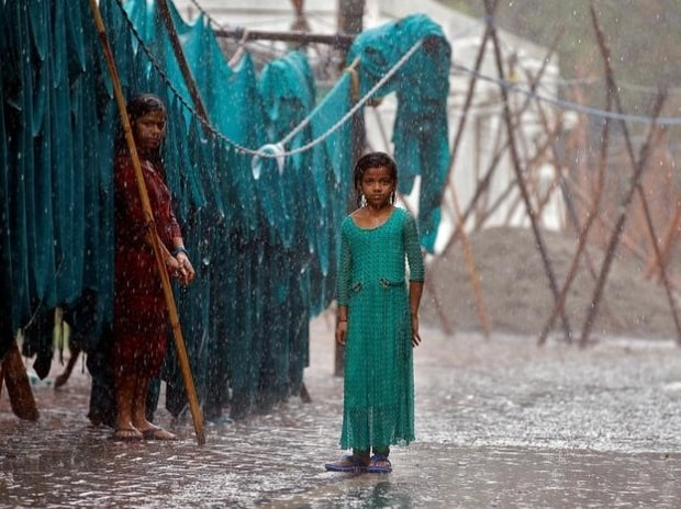 Two girls standing beside an open laundry, while it rains in New Delhi in India. (Photo: Reuters)