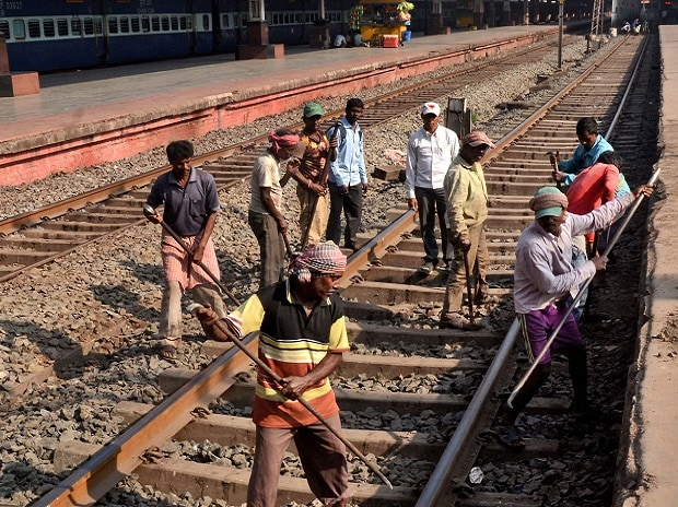 Railway workers busy in maintenance work at rail track in Howrah railway station near Kolkata on Saturday. (Photo: PTI)