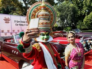 Folk artists take selfie as they perform in front of Vintage Cars