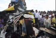 People looking at the damaged school bus that was hit by a train at Masaipet in Medak