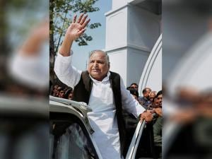 Samajwadi Party leader Mulayam Singh Yadav waves to supporters after casting his vote
