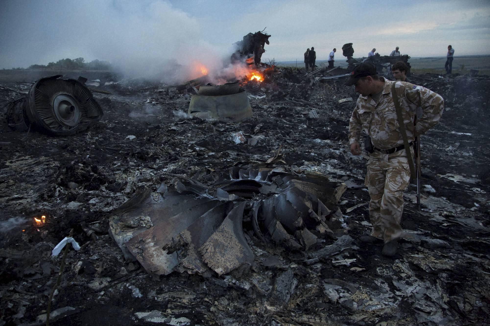 man, walks, debris,crash site, passenger plane, village,  Hrabove, Ukraine, shot down, flew, country, government , pro-Russia, separatists, fighting, region denied, responsibility, the plane