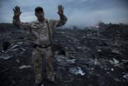 A man gestures at a crash site of a passenger plane near the village of Grabovo