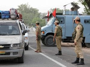 Security personnel on Jammu-Srinagar National Highway closed for traffic during a terrorist was killed in a gunbattle with CPRF jawans at a joint CRPF-Police camp in Kud