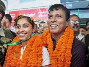 Gymnast Dipa Karmakar with her coach Bisweswar Nandi being welcomed on her arrival at the airport in Agartala