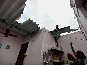 A man repairing the broken roof of the house as a woman looks on following the cyclone Vardah