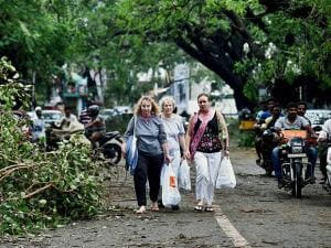 Foreign nationals walking at an arterial road in Adyar that bears the brunt of cyclone Vardah