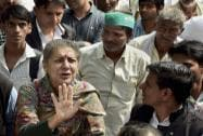 Congress leader Ambika Soni stands in public as she arrives to participate in an agitation against land acquisition ordinance