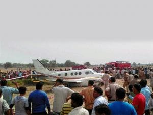 People looking at the air ambulance which crash landed at Kair village in Najafgarh area of Delhi