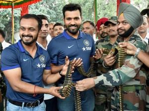 Rohit Sharma and Ajinkya Rahane trying to know about the functioning of a mortar shell launcher as they spend time with the soldiers