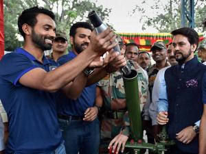 Rohit Sharma and Ajinkya Rahane trying to know about the functioning of a mortar shell launcher as they spend time with the soldiers of 124 Sikh Battalion