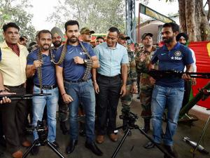 Rohit Sharma, Kedar Jadhav, Manish Pandey and Ajinkya Rahane hold a chain of bullets and weapons as they spend time with the soldiers of 124 Sikh Battalion