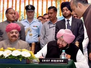 Amarinder Singh signs a document after taking oath as the Chief Minister of Punjab