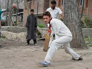 A double arm amputee Amir Hussain Lone bats the ball while playing a practice match in his village Waghama