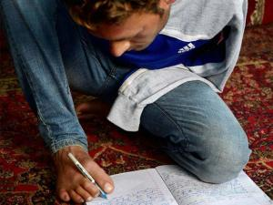 A double arm amputee Amir Hussain Lone uses his feet to write, in his village Waghama, Anantnag on Sunday. Amir does all other activities by using his feet and toes