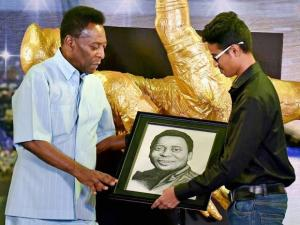 Legendary Brazilian footballer Pele receives a pencil sketch of his from a student