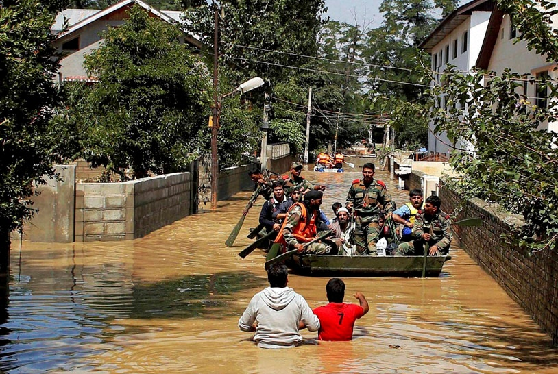 Volunteers, back towards camera, give, directions, Indian army soldiers, trying, rescue, flood, affected, people, Srinagar