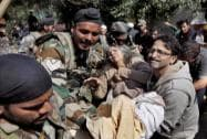 Army soldiers and civilians rescue an elderly flood victim in Srinagar
