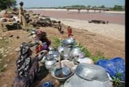 Nomadic gujjars sit with their belongings on the banks of the Tawi River