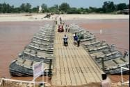 People use a temporary bridge built by the army to cross the Tawi River in Jammu