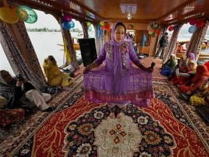 Kashmiri folk artists perform on a dunga cruise during the two day tourism festival at Dal Lake in Srinagar.