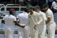 Australia's bowler Nathan Lyon shakes wand with West Indies' Veerasammy Permaul,