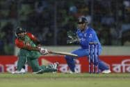 Bangladesh's Litton Das, left, plays a shot, as India's captain M S Dhoni