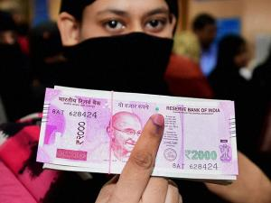 A woman shows her inked finger after exchanging 500 and 1000 rupee currency notes at a SBI bank