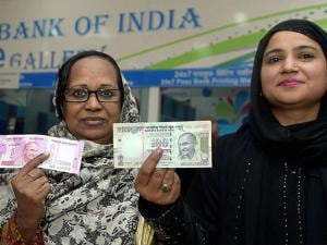 Women shows thier inked finger after exchanging 500 and 1000 rupee currency notes at a SBI bank in New Delhi