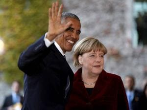 U.S. President Barack Obama waves as he is welcomed by German Chancellor Angela Merkel