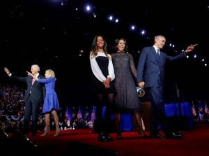 President Barack Obama points on stage with first lady Michelle Obama