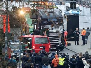 Media people stand near a truck which ran into a crowded Christmas market