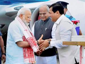 Prime Minister Narendra Modi being greeted by Assam Chief Minister Sarbananda Sonowal